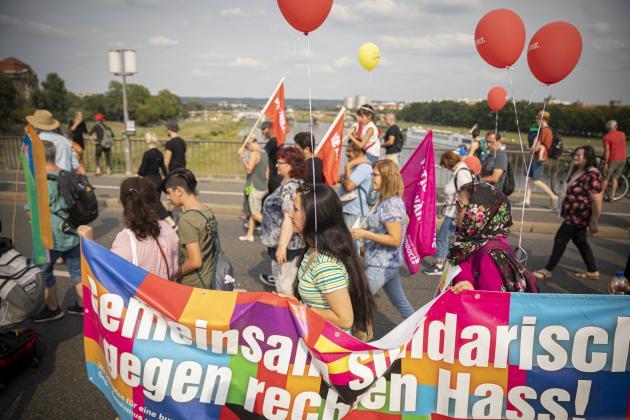 Menschen demonstrieren mit einem bunten Banner und Luftballons gegen Rassismnus