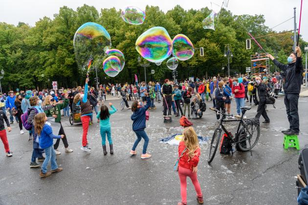 Kinder auf einer Straße mit riesigen Seifenblasen