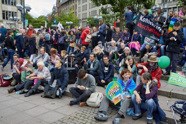 Menschen mit Plakaten sitzen auf der Straße