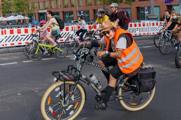 Ältere Frau in oranger Warnweste auf Fahrraddemo